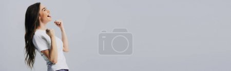 Photo for Side view of excited happy beautiful girl in white t-shirt showing yes gesture isolated on grey, panoramic shot - Royalty Free Image