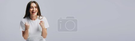 Photo for Happy pretty girl in white t-shirt showing yes gesture isolated on grey, panoramic shot - Royalty Free Image