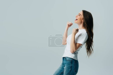 Photo for Side view of happy beautiful girl in white t-shirt showing yes gesture isolated on grey - Royalty Free Image