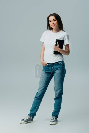 Photo for Happy beautiful girl in white t-shirt and jeans with notebook isolated on grey - Royalty Free Image