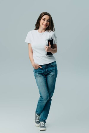 Photo for Happy beautiful girl in white t-shirt and jeans holding notebook isolated on grey - Royalty Free Image