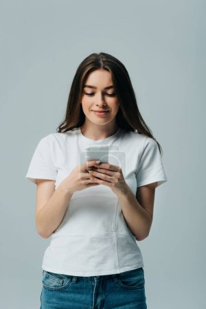 Photo for Smiling beautiful girl in white t-shirt using smartphone isolated on grey - Royalty Free Image