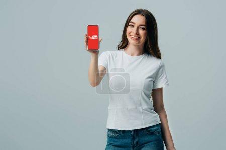 Photo pour Kiev, Ukraine - 6 juin 2019: belle fille heureuse dans le t-shirt blanc affichant le smartphone avec l'application de youtube d'isolement sur le gris - image libre de droit