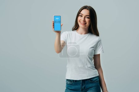 Photo pour Kiev, Ukraine - 6 juin 2019: belle fille heureuse dans le t-shirt blanc affichant le smartphone avec l'application de skype d'isolement sur le gris - image libre de droit