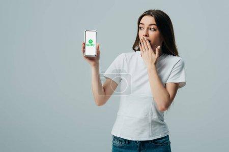 Photo pour Kiev, Ukraine - 6 juin 2019: belle fille choquée en t-shirt blanc montrant smartphone avec l'application Spotify isolée sur le gris - image libre de droit
