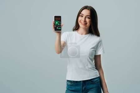 happy beautiful girl in white t-shirt showing smartphone with marketing analysis app isolated on grey