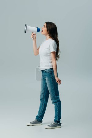 Photo for Side view of young pretty woman with loudspeaker isolated on grey - Royalty Free Image