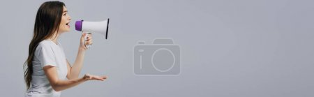 Photo for Young pretty woman speaking in loudspeaker isolated on grey, panoramic shot - Royalty Free Image
