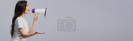 Photo pour Jeune jolie femme parlant dans le haut-parleur isolé sur le gris, projectile panoramique - image libre de droit