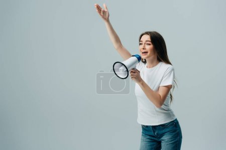 Photo for Cheerful young pretty woman speaking in loudspeaker with hand in air isolated on grey - Royalty Free Image