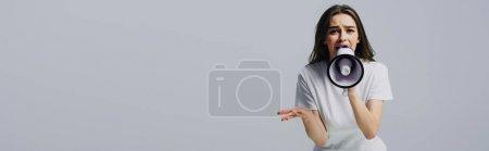 Photo pour Jeune jolie femme criant dans le haut-parleur isolé sur le gris, projectile panoramique - image libre de droit