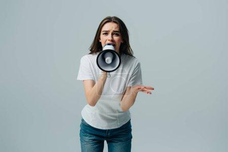 Photo pour Jeune femme jolie émotive criant dans le haut-parleur isolé sur le gris - image libre de droit