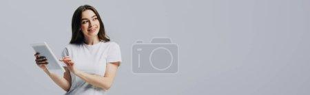 Photo pour Heureuse fille en t-shirt blanc tenant tablette numérique et regardant loin isolé sur gris, panoramique shot - image libre de droit