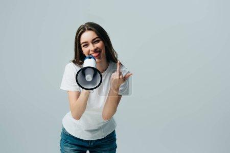 Photo pour Jeune femme jolie heureuse avec le haut-parleur affichant le doigt moyen d'isolement sur le gris - image libre de droit
