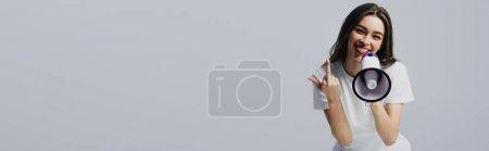 Photo pour Jeune femme heureuse jolie avec le haut-parleur affichant le doigt moyen d'isolement sur le gris, projectile panoramique - image libre de droit