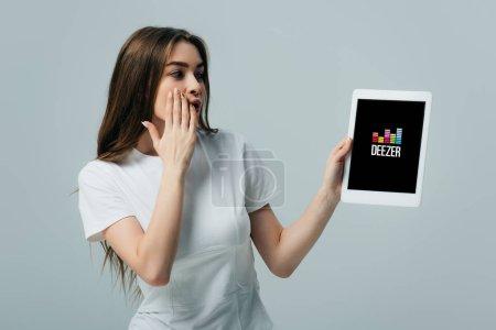 Photo pour Kiev, Ukraine - 6 juin 2019: belle fille choquée en t-shirt blanc montrant tablette numérique avec application deezer isolé sur le gris - image libre de droit