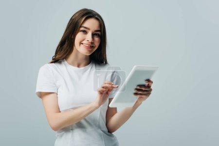 Photo pour Heureuse fille en t-shirt blanc tenant tablette numérique isolé sur gris - image libre de droit