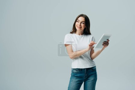 happy girl in white t-shirt holding digital tablet and looking away isolated on grey
