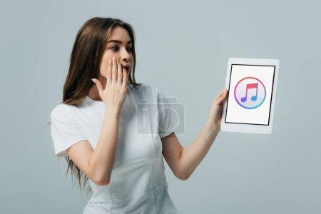 Photo pour Kiev, Ukraine - 6 juin 2019: belle fille choquée en t-shirt blanc montrant tablette numérique avec l'application Apple Music isolée sur le gris - image libre de droit