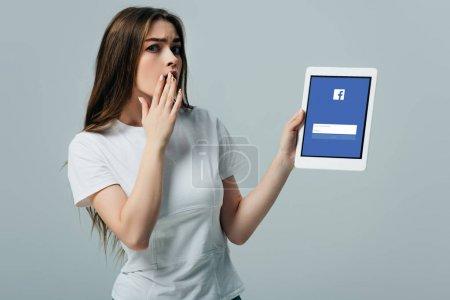 kyiv, ukraine - 6. Juni 2019: Schockiertes schönes Mädchen in weißem T-Shirt zeigt digitales Tablet mit Facebook-App isoliert auf grau