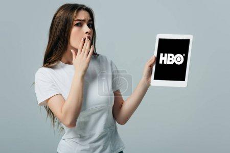 Photo pour KYIV, UKRAINE - 6 JUIN 2019 : belle fille choquée en t-shirt blanc montrant tablette numérique avec application HBO isolée sur gris - image libre de droit