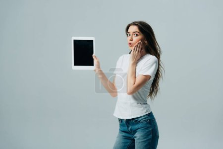 Photo for Shocked pretty girl in white t-shirt showing digital tablet with blank screen isolated on grey - Royalty Free Image