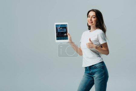 Photo pour Sourire belle fille en t-shirt blanc montrant tablette numérique avec application de réservation en ligne et montrant pouce vers le haut isolé sur gris - image libre de droit