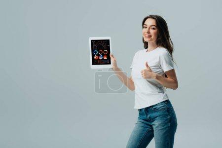 Photo pour Belle fille de sourire dans le t-shirt blanc affichant la tablette numérique avec l'application financière et le pouce vers le haut d'isolement sur le gris - image libre de droit