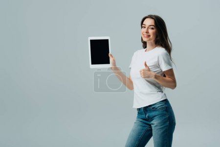 Photo for Smiling beautiful girl in white t-shirt showing digital tablet with blank screen and thumb up isolated on grey - Royalty Free Image