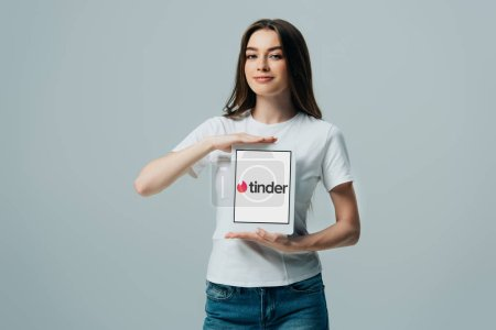 Photo pour KYIV, UKRAINE - 6 JUIN 2019 : belle fille souriante en t-shirt blanc montrant tablette numérique avec application Tinder isolée sur gris - image libre de droit