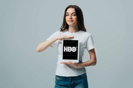 Photo pour KYIV, UKRAINE - 6 JUIN 2019 : belle fille souriante en t-shirt blanc montrant tablette numérique avec application HBO isolée sur gris - image libre de droit