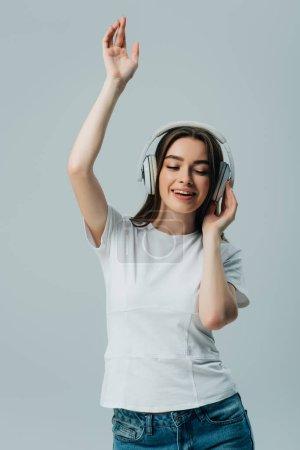 Photo pour Jolie fille heureuse écoutant la musique dans le casque sans fil et dansant d'isolement sur le gris - image libre de droit
