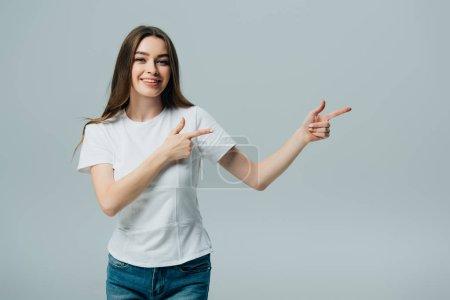 Photo pour Belle fille heureuse pointant avec les doigts à l'espace de copie isolé sur gris - image libre de droit