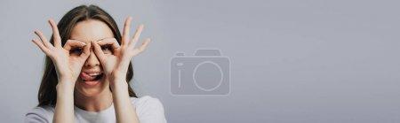 Photo pour Plan panoramique de belle fille heureuse montrant la langue et ok signes isolés sur gris - image libre de droit