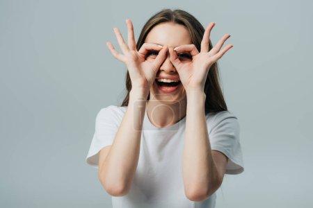 Photo pour Belle fille heureuse montrant ok signes isolés sur gris - image libre de droit