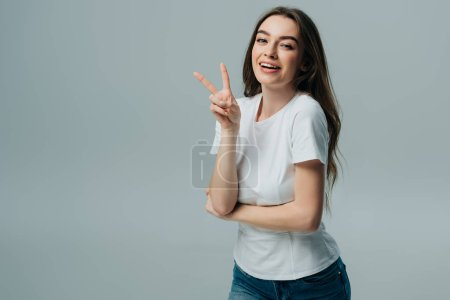 Photo for Beautiful happy girl showing peace sign isolated on grey - Royalty Free Image