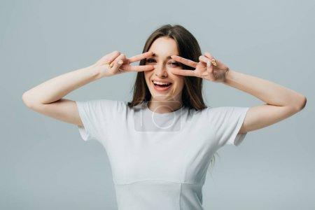 Photo pour Belle fille heureuse affichant des signes de paix d'isolement sur le gris - image libre de droit