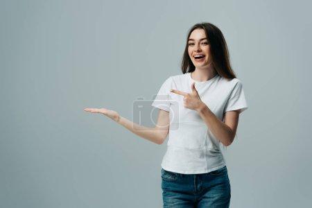 Photo pour Belle fille excitée pointant avec la main et le doigt à l'espace de copie isolé sur gris - image libre de droit