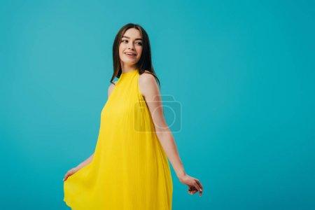 Photo pour Fille heureuse dans la robe jaune tournant autour d'isolement sur le turquoise - image libre de droit