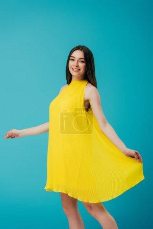 Photo pour Belle fille heureuse de sourire dans la robe jaune d'isolement sur le turquoise - image libre de droit