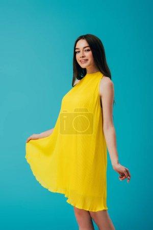 Photo pour Heureuse belle fille en robe jaune isolé sur turquoise - image libre de droit