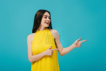 Photo pour Heureuse belle fille en robe jaune pointant avec les doigts et regardant loin isolé sur turquoise - image libre de droit