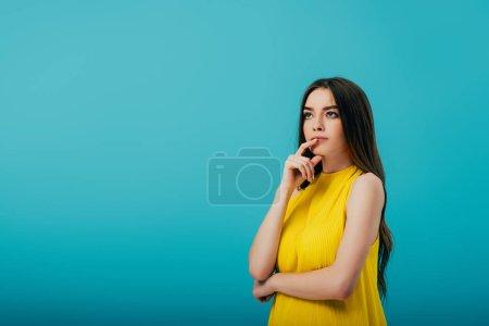 Photo pour Réfléchie belle fille en robe jaune regardant loin sur turquoise - image libre de droit