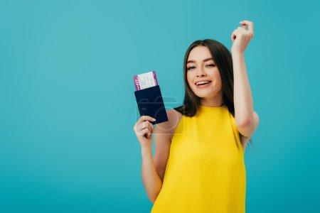 Photo pour Femme gaie de brunette dans la danse jaune de robe avec le passeport avec le billet d'avion d'isolement sur le turquoise - image libre de droit