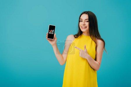 Photo pour KYIV, UKRAINE - 6 JUIN 2019 : heureuse belle fille en robe jaune pointant du doigt le smartphone avec application Deezer isolée sur turquoise - image libre de droit