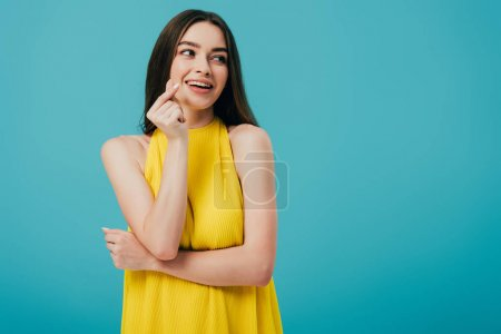 Photo for Happy brunette girl in yellow dress snapping fingers isolated on turquoise - Royalty Free Image