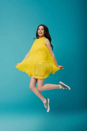 Photo pour Vue pleine longueur de la fille heureuse dans la robe jaune sautant sur le fond turquoise - image libre de droit