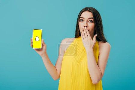 Photo pour Kiev, Ukraine - 6 juin 2019: belle fille choquée en robe jaune montrant smartphone avec l'application Snapchat isolée sur turquoise - image libre de droit