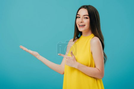 happy beautiful girl in yellow dress pointing with finger at copy space isolated on turquoise