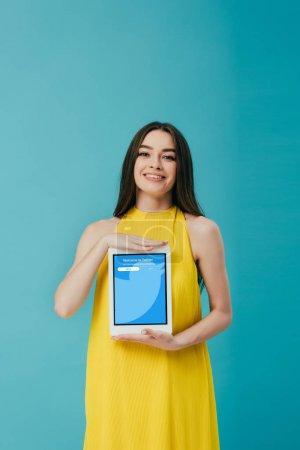 Photo pour KYIV, UKRAINE - 6 JUIN 2019 : belle fille souriante en robe jaune montrant tablette numérique avec application twitter isolée sur turquoise - image libre de droit